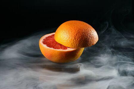 Ice cold grapefruit in fragrant smoke Stock Photo - 137755050