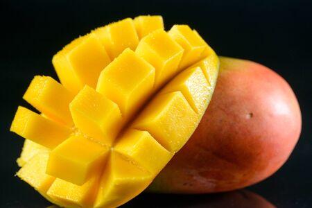 Juicy fragrant mango on glass black background Stock Photo