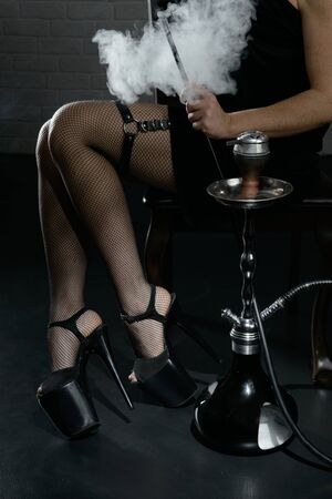 Beautiful female legs in high heel shoes in smoke