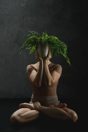 Woman meditates in yoga pose with plant Zdjęcie Seryjne