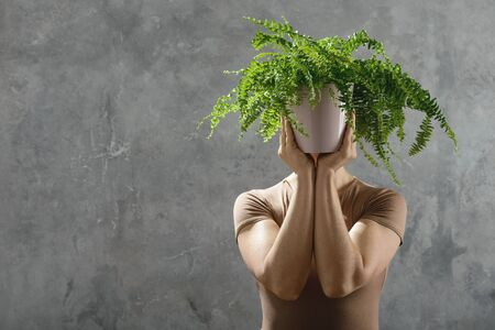Woman holds a plant in her hands Stock Photo