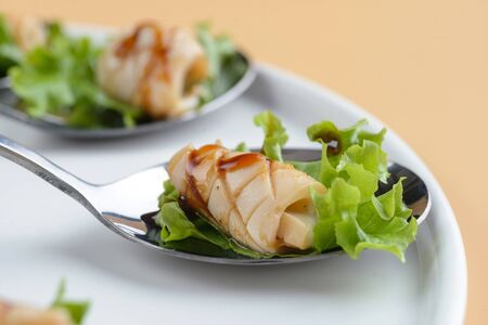 Squid snack with salad garnished on spoon
