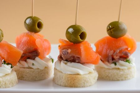 Canape with red fish, olives and cream cheese on white plate 写真素材