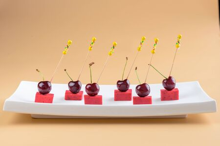 Canape with cherries and cheese on a white plate