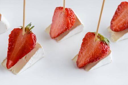 Canape with strawberries and camembert cheese on white plate