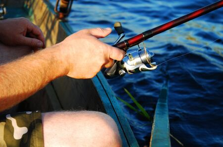 Hands holding a fishing rod by the sea photo