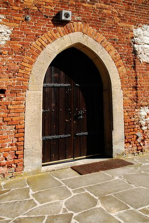 old door of the ancient prison brick wall photo