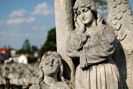 angel statue in cemetery, trees and blue sky  Stock Photo