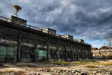 Old shut down factory is overshadowed by dark stormy clouds Stock Photo