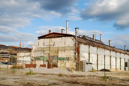 shut down: Old shut down factory is overshadowed by dark stormy clouds Stock Photo