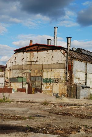 Old shut down factory is overshadowed by dark stormy clouds photo