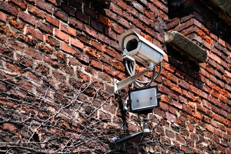 Security camera on a red brick wall. Stock Photo