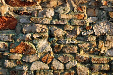 irregular shapes: Traditional stone brick wall made of fragment stones in irregular shapes.