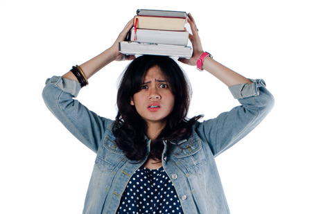 Young college girl so depressed with so many book Banco de Imagens