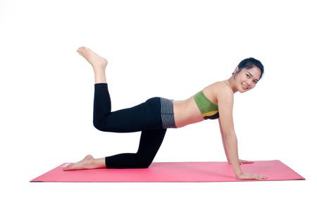 yoga pants: Beautiful woman indoor exercising using pink yoga mat Stock Photo