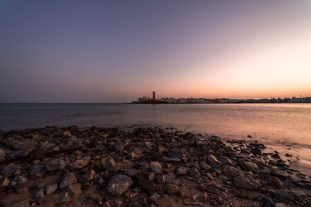 Sunrise on a rocky beach with a lighthouse in the background at Sur's bay, Oman