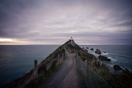 Gorgeous pink sunrise panorama at Nugget Point Lighthouse taken on a cloudy winter day, New Zealand