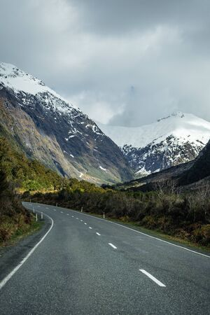 Splendid image of the SH94 road towards Milford Sound surrounded by greenery with snow capped mountains in the background taken on a sunny winter day, New Zealand Archivio Fotografico