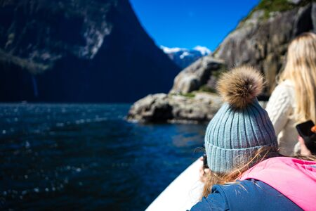 Milford Sound, New Zealand, October 5, 2019: Gorgeous image of a blonde girl with skullcap on her back admiring the snowy mountains on a sunny winter day