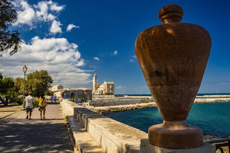 Two lovers walk, holding hands, in the municipal park of Trani, with the view of the sea and the Cathedral Basilica of St. Nicholas Pilgrim in the background. In Puglia, near Bari, Barletta, Andria.