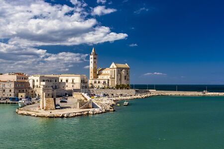 The beautiful Romanesque Cathedral Basilica of San Nicola Pellegrino, in Trani. Construction in limestone tuff stone, pink and white. A pointed arch under the bell tower. Italy, Puglia, Bari, Barletta Stock fotó