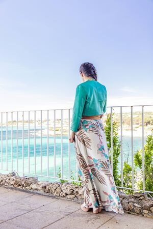 A young and beautiful woman, alone in a luxury hotel, contemplates, thoughtfully, the panorama of the turquoise sea, in Salento, Puglia, Italy. Elegant dress with green jacket. Terrace on the sea.