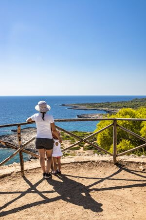A mother and her little daughter admire the landscape and the view of the sea, from above, on a panoramic terrace. In summer, in Porto Selvaggio, Salento, Lecce, Puglia, Italy. Amazing panorama.
