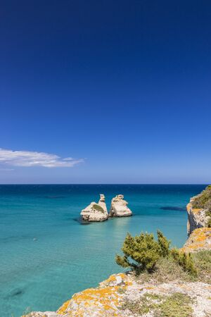 The bay of Torre dell'Orso, with its high cliffs, in Salento, Puglia, Italy. Turquoise sea and blue sky, sunny day in summer. The stacks called the Two Sisters. A person swims in the clear water