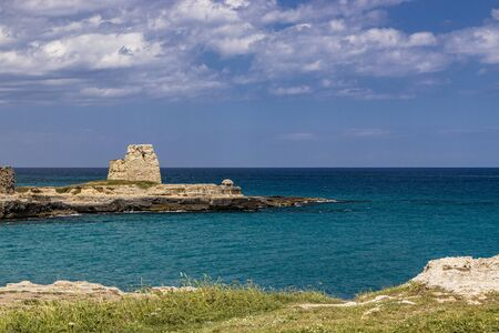 Archaeological site and tourist resort of Roca Vecchia, Puglia, Salento, Italy. Turquoise sea, clear blue sky, rocks, sun, in summer. The sixteenth-century lookout tower. White clouds and strong wind.