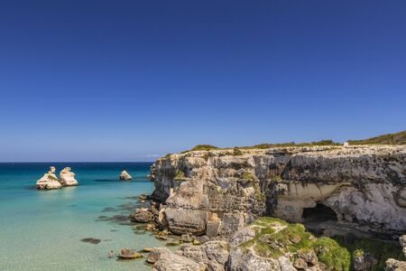 The bay of Torre dell'Orso, with its high cliffs, in Salento, Puglia, Italy. Turquoise sea and blue sky, sunny day in summer. The stacks called the Two Sisters, immersed in the sea. Фото со стока