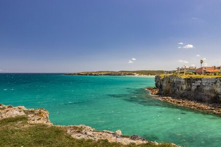 The bay of Torre dell'Orso, with its high cliffs, in Salento, Puglia, Italy. Turquoise sea and blue sky, sunny day in summer. Some houses above the reef Stock Photo