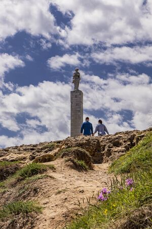 The important archaeological site of Roca Vecchia, in Puglia, Salento, Italy. blue sky, rocks, sun, lush vegetation in summer. The column of Santa Maria di Roca. A couple of tourists holding hands Stock Photo