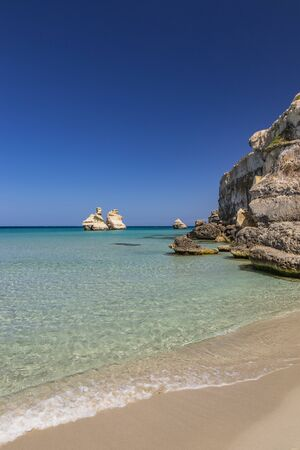 The bay of Torre dell'Orso, with its high cliffs, in Salento, Puglia, Italy. Turquoise sea and blue sky, sunny day in summer. A beach of fine white and pink sand. The stacks called the Two Sisters.