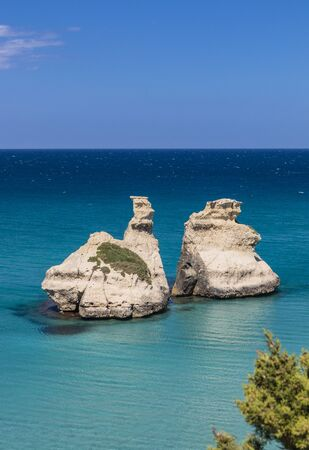 The bay of Torre dell'Orso, with its high cliffs, in Salento, Puglia, Italy. Turquoise sea and blue sky, sunny day in summer. The stacks called the Two Sisters, immersed in the sea.