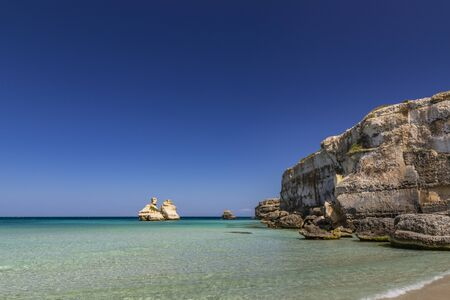 The bay of Torre dell'Orso, with its high cliffs, in Salento, Puglia, Italy. Turquoise sea and blue sky, sunny day in summer. A beach of fine white and pink sand. The stacks called the Two Sisters. Archivio Fotografico