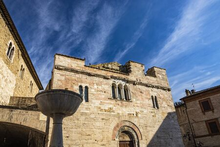 The medieval Palazzo dei Consoli in the village of Bevagna. Brick and stone wall and mullioned windows. The Romanesque Church of San Silvestro. The marble fountain. Perugia, Umbria, Italy.