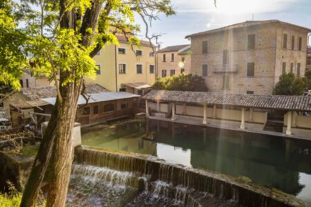 The ancient wooden wash house, on the river, in the medieval village of Bevagna. Umbria, Italy. The blue sky at sunset. Trees and vegetation. The reflection of the buildings on the water surface.