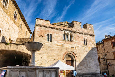 June 1, 2019 - Bevagna, Perugia, Umbria, Italy. The medieval Palazzo dei Consoli in the village of Bevagna. Brick and stone wall. The Romanesque Church of San Silvestro. The marble fountain.