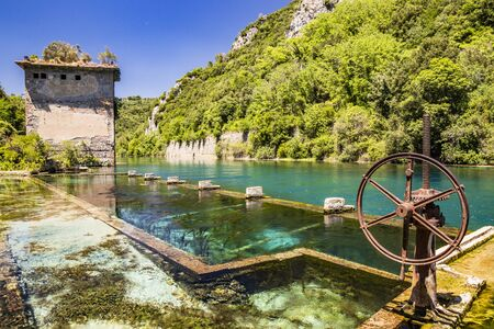 The Roman port of ancient Narnia (Narni), in Stifone, in the canyons of the Nera river. The blue sky and the clear, cold and turquoise water, on a sunny day, in the summer. Wild and pristine nature.