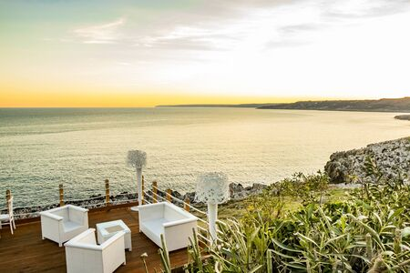 Italian restaurant with panoramic terrace, with spectacular view of the blue sea at sunset. In Puglia, Italy. Wooden terrace with curtains, armchairs, chairs, tables and lamps in white. Stock Photo