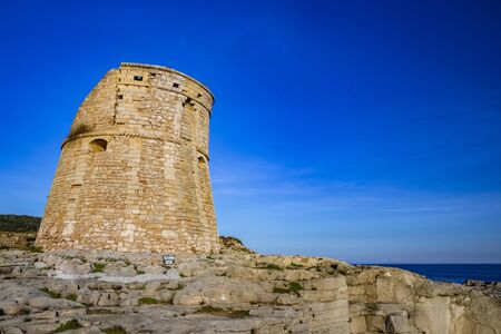 The ancient watch tower of Porto Miggiano, built on the cliffs overlooking the sea. Bleak and rocky landscape with a splendid view of the sea. Santa Cesarea Terme, Puglia, Salento, Italy.