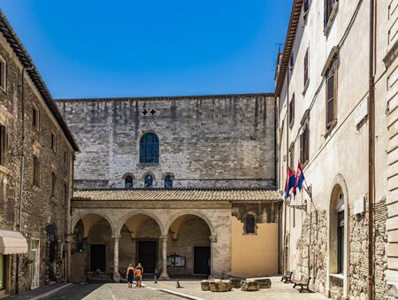 The medieval cathedral of San Giovenale in the ancient village of Narni. The façade with the portico and the entrance to the church. Umbria, Terni, Italy. The blue sky on a summer day.