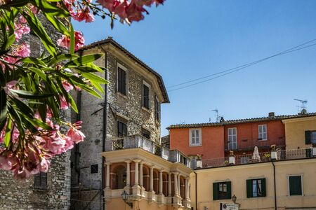 Piazza Garibaldi in the ancient village of Narni, Terni, Umbria, Italy. The ancient stone and brick buildings. The blue sky on a summer day. A flowering tree.
