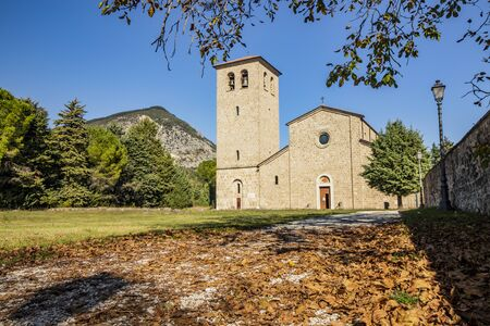 San Vincenzo al Volturno, a Benedictine monastery in Castel San Vincenzo and Rocchetta a Volturno. The new abbey. Dried leaves of a tree fallen on the gravel avenue, in autumn. Fir trees and mountain. 版權商用圖片