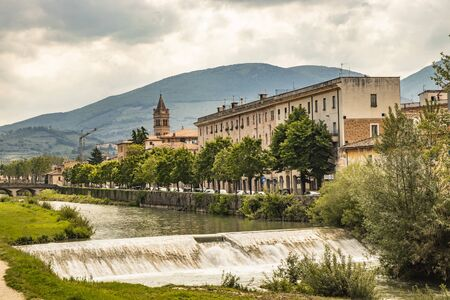 A view of Foligno, crossed by the river Topino, a bell tower rises above the roofs of the houses. The cloudy sky at sunset. The canal, the bridge and the trees.