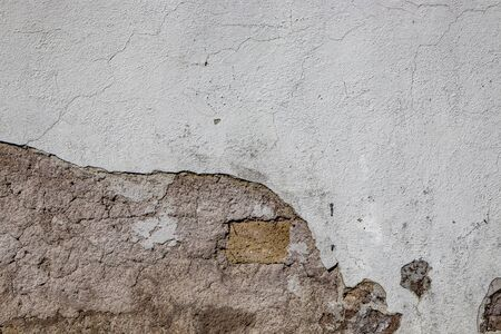 Gray wall ruined by time, bad weather and humidity. Cracks, mold, peeling paint and plaster. Bricks uncovered. Texture, material background.