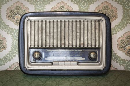An old transistor radio, with knobs and buttons for manual tuning. In the background a vintage wallpaper. Ancient object, worn and ruined by time. Antiques