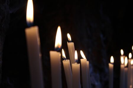 Row of lit candles on offer to the cult of the Virgin Mary (Madonna), in the cave of the sanctuary of the Mentorella, in Guadagnolo. Rome, Lazio, Italy. Sacred place of prayer, peace and silence. Stockfoto