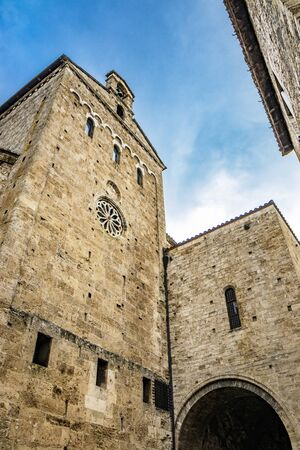 Side facade of the Cathedral Basilica of Santa Maria Annunziata, with the rose window, in Piazza Innocenzo III. Stone buildings from the Middle Ages. Anagni, Frosinone, Italy.