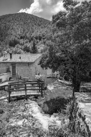 The small village of Rasiglia, crossed by many streams and waterfalls, fed by the Menotre river. A sluice regulates the flow of water. A wooden bridge. Old brick houses. Foligno, Umbria. Banco de Imagens - 148811525